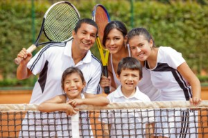 Happy family playing tennis and holding rackets